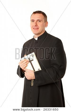 Smiling young priest with bible and rosary in his hands