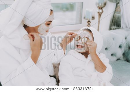 poster of Spa Day In Beauty Salon. Towel On Head. Make Cucumbers Mask. Mom And Daughter In Spa. Consept Beauty
