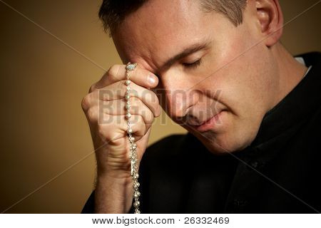 Praying priest with rosary in his hands