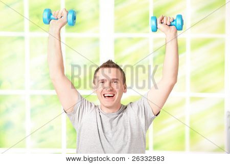 Portrait of happy man working with dumbbells, celebrating succes