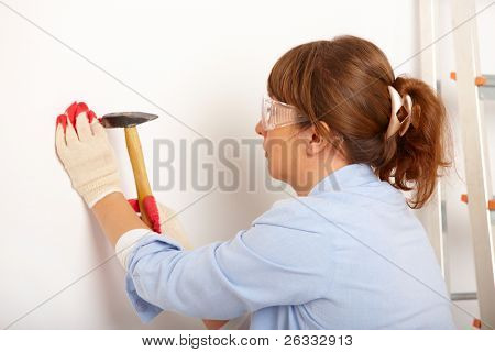 Woman working with hammer driving a nail in white wall in home, wearing protective gloves and glasses