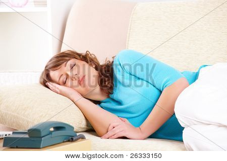 Portrait of a young woman sleeping on sofa. Telephone is also visible.