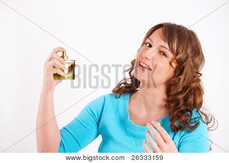 Portrait of young happy woman applying perfume