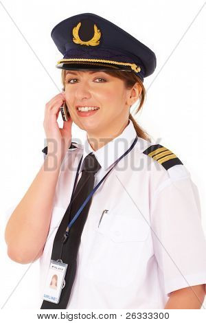 Beautiful woman pilot wearing uniform with epaulettes and hat with golden wings, talking on mobile phone, standing isolated on white background.