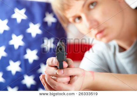 Woman with gun aiming at something, US flag in background