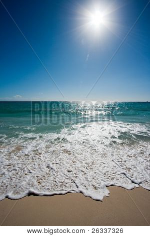Beautiful beach, sun and waves of Caribbean Sea