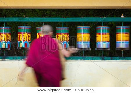 Tibetan Buddhist monk (lama) and prayer wheels