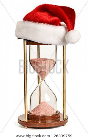 Christmas is coming concept - hourglass  with Santa Claus hat isolated on white background