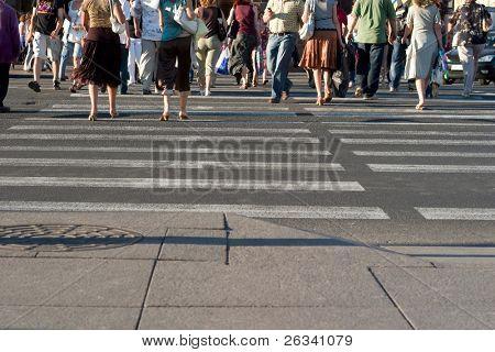 Pedestres atravessando uma rua da cidade grande
