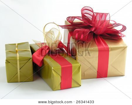 gifts and presents in gold paper with red ribbons under christmas tree