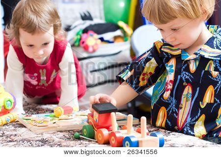 Lindos niños jugando en el jardín de la infancia con los juguetes coloridos