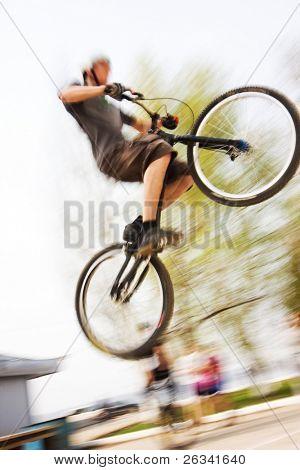 Menino em uma bicicleta de bmx/montanha saltando. Motion blur foto f / x