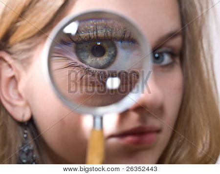 Girl looking into magnifying glass