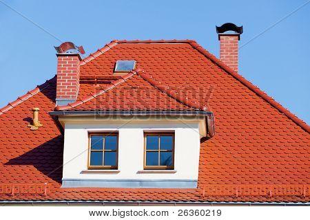 Flashing orange tiled roof on blue sky