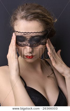 woman in black corset wearing delicate lace on her eyes