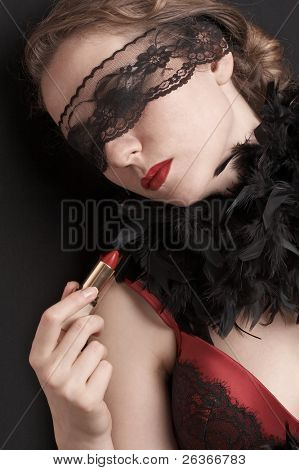 red lipstick; woman in red corset wearing delicate lace on her eyes