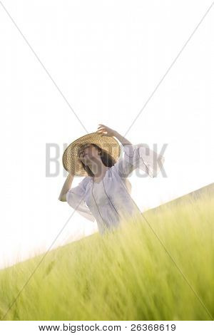 blond girl  with big hat having fun in a green wheat field