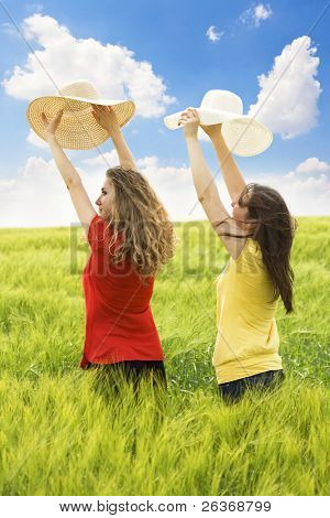two girls in a wheat field, two friends enjoying the open air