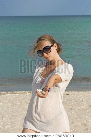 blond woman on the beach holding seashells in her hand