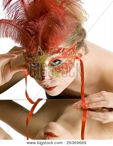 woman with red carnival mask looking in the mirror