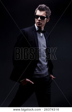 fashion shot of an elegant young man wearing suit and bow tie