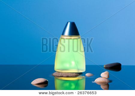 Yellow phial and  several stones in the water.