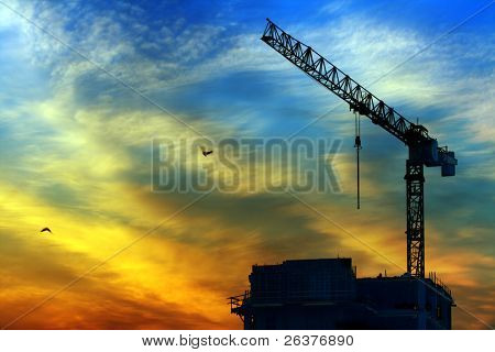 Beautiful sky at sunrise in city. Building under construction and crane. Also two flying birds.