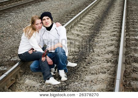 Young couple sitting on railway tracks