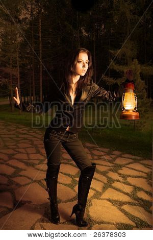 Young woman sneak with old oil lamp outdoor at night. Image with clipping path
