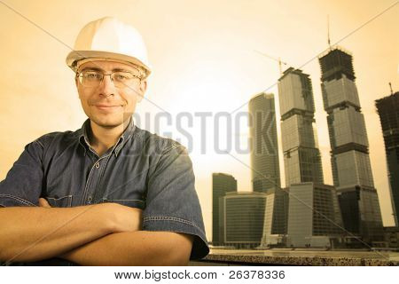 The architect wearing a protective helmet standing in front of a building site