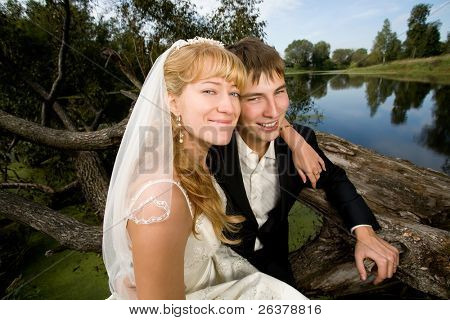 the newly married couple sitting  at fallen tree near water