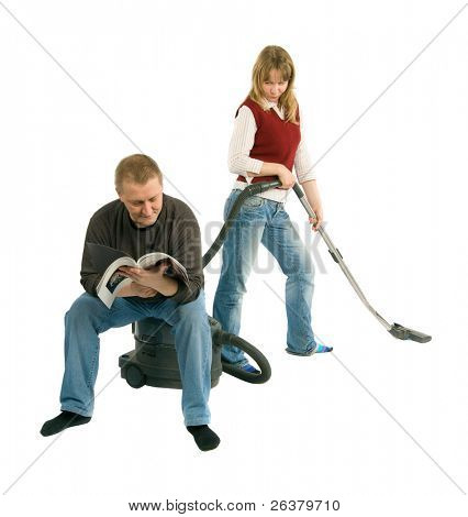 The man is sitting on the vacuum-cleaner and reading a magazine, while the woman is hovering. She makes stop and looks at him slyly.