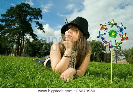 One girl is laying on the meadow near toy colors windmill with a little green flower in her mouth