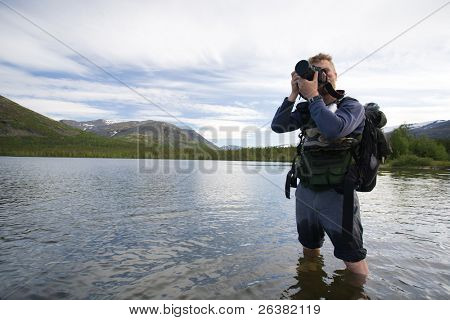 Tourist taking pictures of mountains and standing at lake