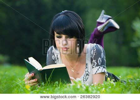 Young brunette woman lying on grass and reading a poetry in spring park