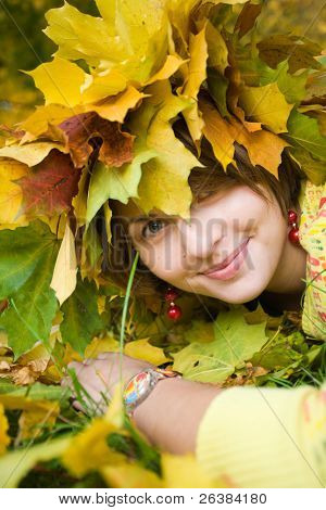 Young beautiful homely woman with crown of maple leaves in autumn park