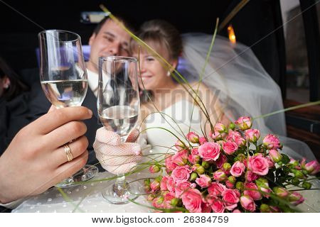 Just married young couple inside limo with flowers and champagne