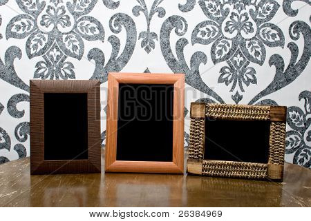 Three wooden photo frames on old table on vintage wallpaper background