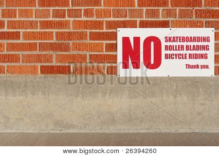 no skateboarding rollerblading or bicycle riding sign on a brick wall