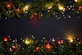 Christmas and New Year background with copy space for text. Fairy lights and decor of fir branches a poster