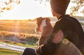 Hugging A Dog In Beautiful Nature At Sunset. Woman Facing Evening Sun Sits With Her Pet Next To Her  poster