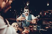 Bartender In Halloween Costume Making Cocktail. Portrait Of Young Man Wearing Costume Standing At Ba poster