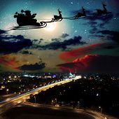 silhouette of a flying goth santa claus against the background of the night sky. Elements of this im poster