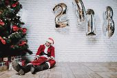 Drunk Santa Claus Near New Year Tree After Party. Christmas Tree In Office. Celebrating Of New Year. poster