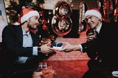 Businessmen In Red Cap In Office On New Year Eve. Gift Box. Christmas Tree In Office. Business Conce poster