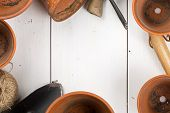 Group Of Empty, Used Terracotta Planting Pots With Gardening Tools On White Wooden Table From Above  poster