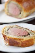 stock photo of beef wellington  - Slice of rare Beef Wellington on the plate closeup - JPG