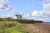 stock photo of beach-house  - An old wooden house alone on a shoreline cliff in rural Prince Edward Island - JPG