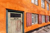 Closed Door Of Colorful Building In Traditional Style In Copenhagen, Denmark. Grunge Texture Of Yell poster