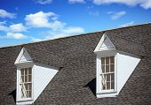 Two White Wood Dormers On A Grey Shingle Roof Under Blue Sky poster